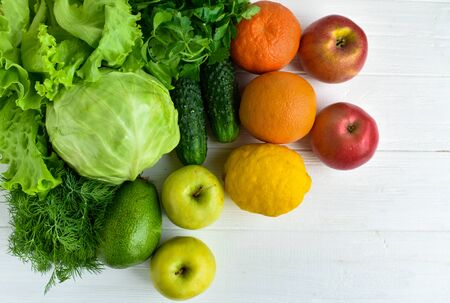 Green cabbage, parsley, cucumbers, salad, avocado, apple, orange orange, mandarin, yellow lemon, red apples on a white wooden background. Healthy eating concept Vegetarianism