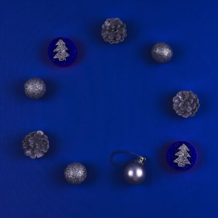 Circle of Christmas toys and cones on a blue background. Color of the year 2020. Trend of the year. Banco de Imagens
