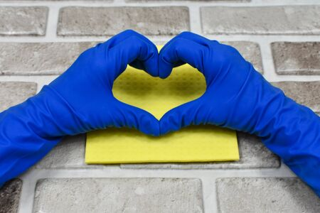 Working hands in rubber protective gloves show the heart. Early spring or regular cleaning. The concept of cleanliness.