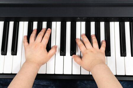 Hands of a young child playing the piano. Learning to play the piano. Studying at home. To stay home. View from above.