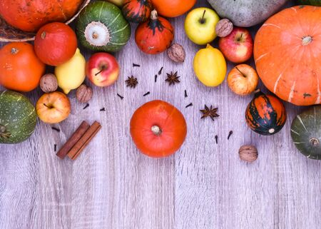 Autumn background from fruits on a wooden background. Autumn background concept. Pumpkin, apples, lemon, nuts. Фото со стока
