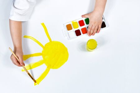 Childrens hands are painted with a brush and watercolors. Childrens creativity, painting, early development.