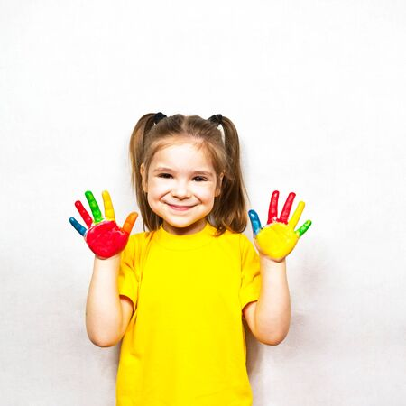 Beautiful little girl with hands in paint smiles in a yellow T-shirt. Childrens creativity.