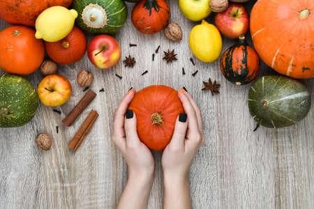 Female hands hold a pumpkin on a background of autumn. Autumn background from pumpkins and fruits on a wooden background. Autumn background concept. Pumpkin, apples, lemon, nuts