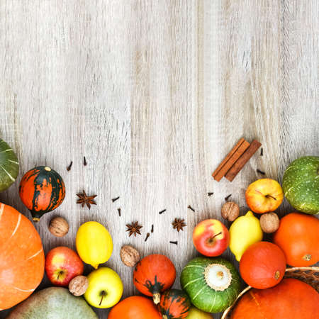 Autumn background from fruits on a wooden background. Autumn background concept. Pumpkin, apples, lemon, nuts.