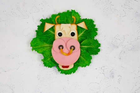 Funny sandwich with edible bull symbol of 2021 made of toast bread, sausage and egg on green lettuce leaves. Breakfast idea for children. New Years Christmas food top view. holiday, holiday, culinary arts