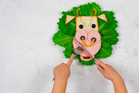 Funny sandwich with edible bull symbol of 2021 made of toast and sausage on green lettuce leaves. Childrens hands are holding a fork and knife. Breakfast idea for children. New Year, Christmas food. Stock Photo