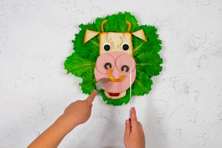 Funny sandwich with edible bull symbol of 2021 made of toast and sausage on green lettuce leaves. Childrens hands are holding a fork and knife. Breakfast idea for children.