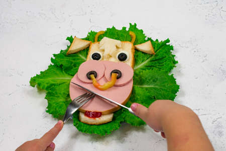 Funny sandwich with edible bull symbol of 2021 made of toast and sausage on green lettuce leaves. Childrens hands are holding a fork and knife. Breakfast idea for children. New Year, Christmas food. Banque d'images