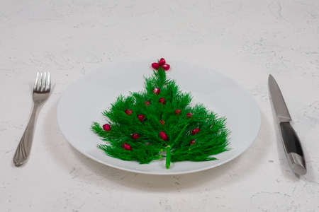 The Christmas tree is lined with green dill, decorated with red pomegranate berries on a white plate with a fork and a knife. Food for the New Year. Table decoration. View from above. Place for an inscription Banque d'images