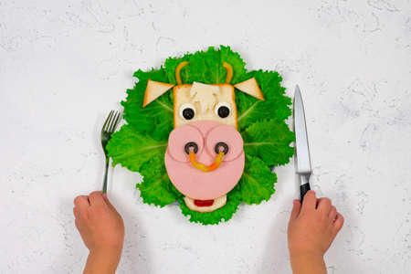 Funny sandwich with edible bull symbol of 2021 made of toast and sausage on green lettuce leaves. Childrens hands are holding a fork and knife. Breakfast idea for children. New Year, Christmas food. 版權商用圖片