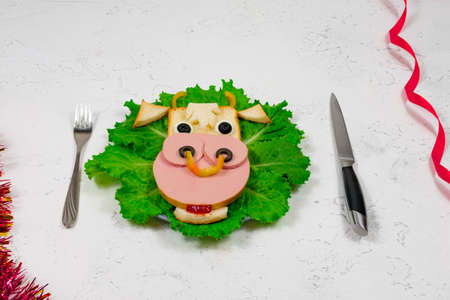 An edible symbol of 2021. Creative children's sandwich in the form of a bull, a cow on a plate. Cute sandwich in the shape of a cow with sausage, olives, cheese, on lettuce leaves. Table, tinsel. New Year's menu. Stock Photo
