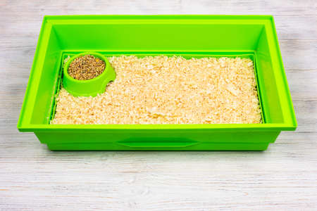 Green pet cage tray with sawdust and food trough.