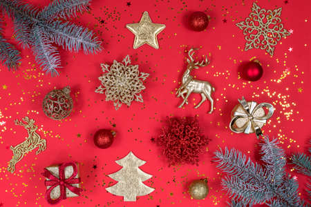 Gold and red Christmas decoration on a red background, top view, flat lay. New Year mood. The basis for the postcard. 版權商用圖片