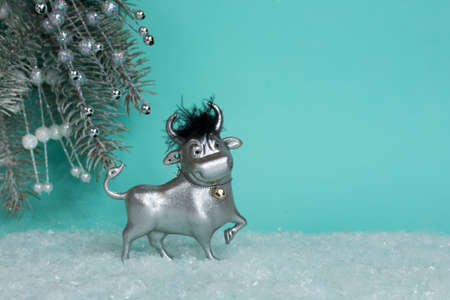 A toy bull on a blue background stands in the snow against the background of a Christmas tree. The symbol of the new 2021. Good New Year mood. Place for an inscription. The basis for the postcard.