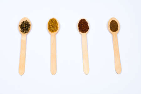 Various spice seeds in wooden spoons on a white background. Seeds of beet, mustard, lettuce, arugula, on a white background. Place for an inscription. View from above.