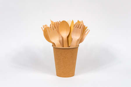 A disposable paper cup with wooden forks and spoons stands on a white background. Place for your text. environmentally friendly concept.