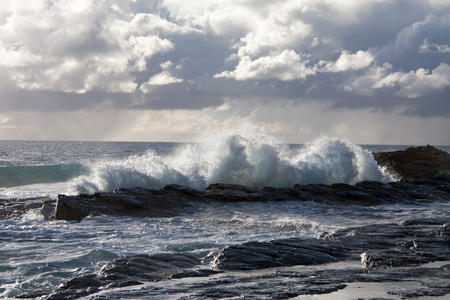 medium waves crashing on the rocks with storm clouds