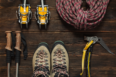 rappel: climbing equipment: red rope, crampons, ice tools, trekking shoes and other set  on dark wooden background, top view. Travel concept.