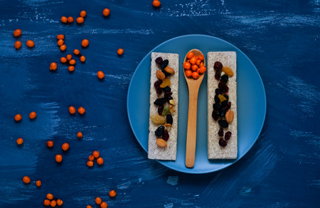 Healthy breakfast, cereal, diet bread on blue background, sea buckthorn in a wooden spoon, closeup, natural light, top view