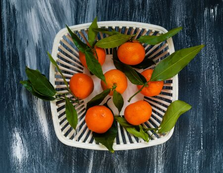 mandarins with green leaves in a white authentic vase for fruit on a blue background