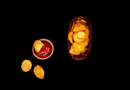 chips   in a basket  with ketchup on a black background, top view, space for text. Convenient snack