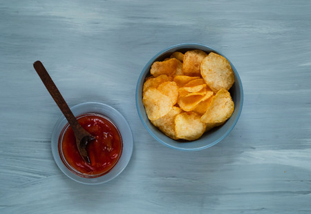 crisps in a blue bowl with ketchup on a light blue background, top view, space for text.Convenient snack concept
