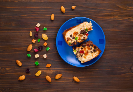 Pieces of homemade muffins with raisins, candied fruits and almonds on a blue plate on a wooden background. Healthy breakfast ingredients, concept of home baked goods, top view, copy space, close up