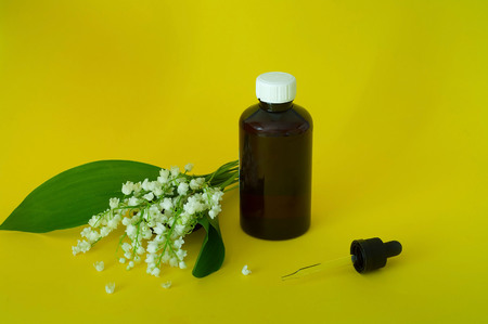 Lily of the valley, essential oil Convallaria majalis (extract, tincture remedy) with fresh flowers Convallaria on a yellow background, concept of ecological ingredients, copy space, close-up Stock Photo
