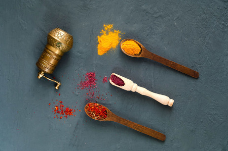 hand mill  and wooden spoons with spices on a dark background. The concept of vegetarian food,  healthy diet, choice of clean food, copy space, closeup. Stock fotó