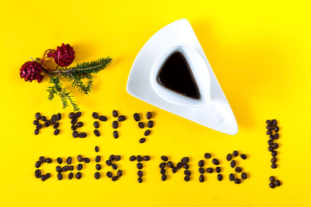 vintage white ceramic cup with coffee and  Inscription of merry Christmas, laid out from the  beans of coffee. Creative yellow background-color of the year 2019,closeup, copy space Stockfoto