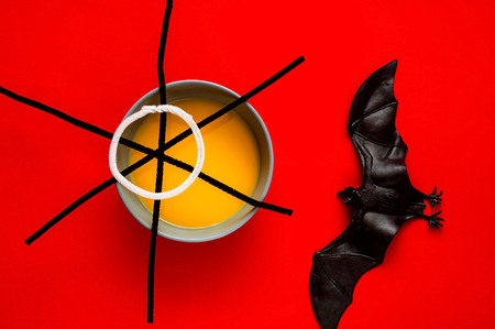 Pumpkin soup in blue bowl isolated on red background, top view. Symbol of HALLOWEEN is black spiderweb and bat , copy space, closeup,