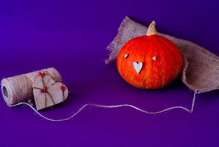 Symbol of HALLOWEEN is Orange pumpkin using the stamp  wooden heart, isolated on purple background,copy space, closeup, Stock Photo