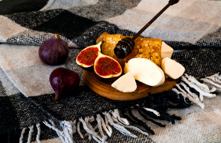 Fresh figs with honey,goat cheese on wooden board.Vegetarian food, concept of natural products. Creative layout of the whole and sliced figs on plaid in Scandinavian style. Copy space, closeup.