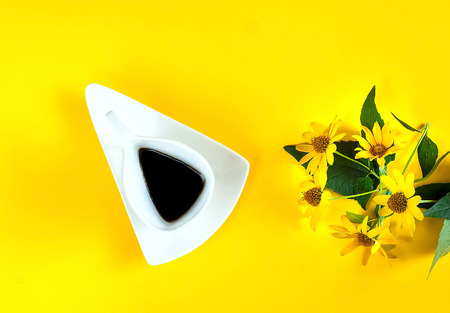 vintage white ceramic cup with coffee and yellow flowers. Creative yellow background-color of the year 2019,closeup, copy space Stockfoto