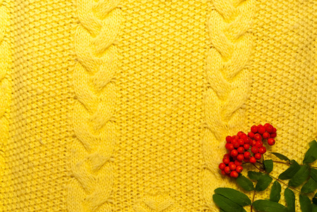 Autumn home decor, background from yellow knitted plaid. Hygge style, the concept of comfort and coziness. Copy space, close up. Stock Photo
