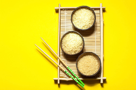Rice in organic coconut bowl with chopsticks on geometric paper background. Yellow  trendy color, close up,copy space