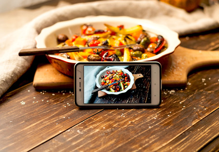 Spicy hot vegetables, cooked on an grill in ceramic bowl on wooden background with smartphone. Food photo for social networks, copy space, closeup 版權商用圖片