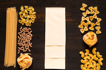 Various uncooked pasta on dark wooden background. Food concept. Flat lay. Top view, copy space.