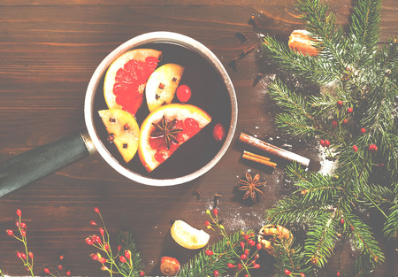 Christmas background. Hot mulled wine with ingredients in authentic ladle on wooden background. The concept of celebration and cooking warming drinks.Top view, close up, copy space Stok Fotoğraf
