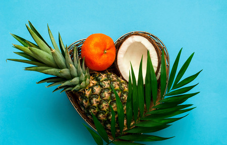 Tropical fruits in wicker basket on blue background.