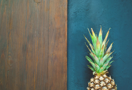 Tropical background with pineapple on blue background. Wooden background for copy space. Closeup, top view.