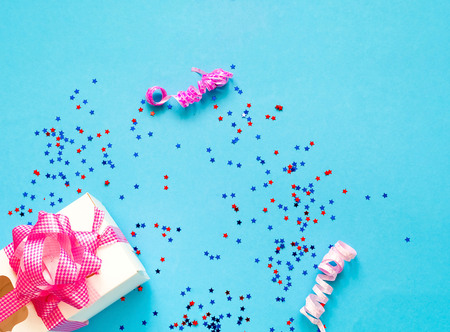 Gift box with pink bow on blue background with sparkles. Festive concept.  Flat lay, top view. Closeup, copy space.