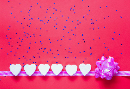 Festive backdrop.  White decorative hearts on coral background with blue sparkles. Love or Valentines Day concept. Flat lay, close up. Top view, copy space.