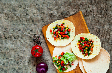 Traditional dish of Mexican cuisine. Corn tortilla tacos with vegetable filling on  burlap texture. Closeup, copy space.