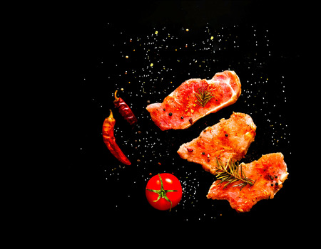 Raw steak  on  black background with spices. Closeup, copy space