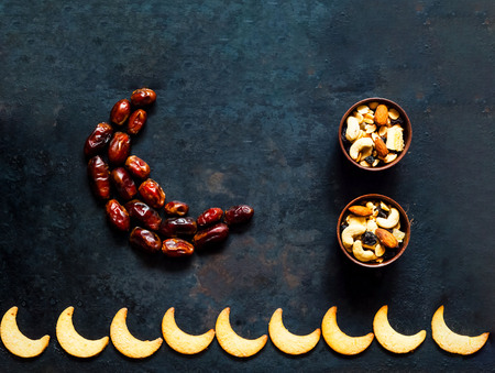 Ramadan kareem. Dates fruit arranged in shape of crescent moon on vintage rusty metal background. Closeup, copy space. Фото со стока