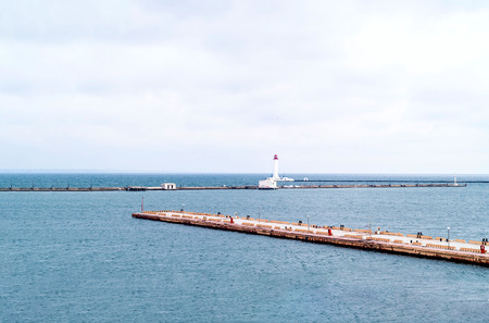 Pier and lighthouse on the background of the sea landscape. Odessa Sea Port. Closeup, copy space.