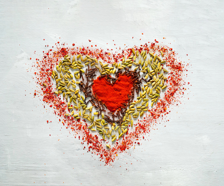 Food background of spices in the shape of heart. Closeup, copy space. Concept of vegetarian food. 스톡 콘텐츠