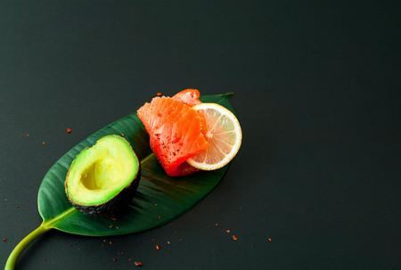 Salmon fillet on tropical leaf on dark background.